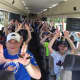 "HHK UnPlugged holds up its ""U"" on the way to the Mets game."