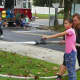 A New Milford girl operates a fire hose with assistance from a firefighter.
