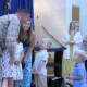Orange County Executive Steve Neuhaus surprising children at a school assembly.