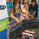 Mary Guerra, left, places her team's remotely operated vehicle (ROV) in the water for demonstration during the May 23 end-of- year celebration for Norwalk teens participating in the TeMPEST after-school program at The Maritime Aquarium at Norwalk.