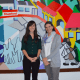 From left, Christa Chu, development and communications manager; and Catalina Horak, executive director of Neighbors Link Stamford.  They are standing in front of a mural created by a Mexican immigrant with help from over 200 volunteers.
