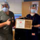 Hospital workers display face shields donated by Hatteras Printing of Tinton Falls.