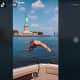 """Donna Paysepar waves to the camera before swan diving into the Hudson River with """"a lot more than Lady Liberty."""""""