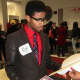 A visitor stops at an information table during College Resource Night Feb. 8 in New Rochelle.