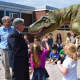 Guy Gsell, Bergen County Executive James Tedesco and Parkway students get an up-close look at a dinosaur.