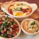 Shakshouka, an egg-based dish, comes with whole wheat pita bread, freshly chopped salad and hummus on the side, at Farmhouse Café & Eatery's brunch.