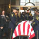 Norwalk police officers prepare to fold a U.S. flag for Lt. Tim Murphy after his Mass of Christian Burial.