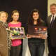 Rye High School students Ellen Scully and Katrina Roth, with City Council Member Julie Killian and Mayor Joe Sack, two members of the panel of judges who picked the winning posters.