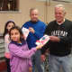 """Students from Parsons Elementary School hand Valentine's Day Cards to Harrison veterans as part of the """"Valentines for Vets"""" program."""