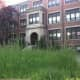 Uncut grass grows tall in front of The Stanwich School at 200 Strawberry Hill Ave. on Thursday. The city has reached an agreement with the owners to buy the 10.8-acre site. Stanwich School had been leasing it but will move its students to Greenwich.