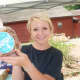 Christine Blaisdell, an employee of the South Norwalk-based Dough & Co., holds up one of its bag of cookies at the Wilton Farmers Market.