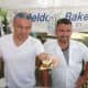 Fernando Castano, left, holds a sample, while Giovanni Castano, owner of Beldotti Bakeries looks on at the Wilton Farmers Market.