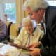 Mayor Steve Ecklond reading the proclamation to Tuckahoe centenarian Mary Finoia.