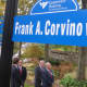 Frank Corvino, Greenwich Hospital President and CEO, front right, standing underneath the street sign for a section of Perryridge Road named in his honor. He is retiring after 26 years with the hospital, the last 23 as its leader.