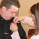 Lisa Hartman pins the sergeant's badge on to her husband David Hartman, who was officially promoted to sergeant in a ceremony Monday at the Wilton Town Hall Annex.