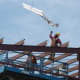 """Construction worker Alejandro Aguilar grabs the ceremonial beam with a Convent of the Sacred Heart flag attached to it during the """"topping off"""" ceremony Thursday for the school's new athletic center."""