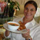 Faina Yelensky, owner of Café Oo La La in Stamford holds up a hot soup and a hot sandwich while hot drink rests nearby.