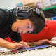 A boy listens to headphones will working on a computer tablet during a Curiosity In Action camp last summer at Fairfield Country Day School.