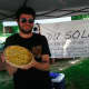 Bobby Goelz, of Du Soleil, holds a quiche at Wednesday's Wilton Farmers Market.