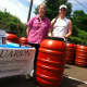 Sharon England, left, owner of SkyJuice New England and Melissa Mickolyzck, of Aquarion, stand beside a water barrel. They are sold by SkyJuice in partnership with Aquarion.