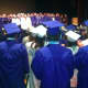 Graduates and others sing the National Anthem at the Darien High School graduation ceremonies.