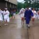 Graduates brave the rain as they walk to Wilton High School on Saturday.