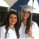 Katherine Kahal, left, and Sarah Stroup stay dry before the Wilton High School graduation ceremonies.