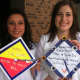 Gabby Pucci, left, and Julia Davatzes hold up their decorated mortarboards.