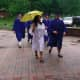 Graduates walk in the rain as they head for Wilton High School to gather for the graduation ceremony.