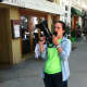 Ann Spallone, district manager for Shoes 'N' More, uses a megaphone to attract customers during the sidewalk sales on Friday.
