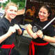 Senseis Shannon Davis, left, and Erika Grieco strike a pose, at the Kempo Academy of Martial Arts tent at the Wilton sidewalk sale event Saturday.