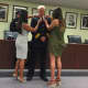 Stamford's new Assistant Chief of Police Tom Wuennemann watches as his daughters, Lauren, 24, left, and Marissa, 22, pin him during his swearing in ceremony Wednesday.