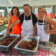 Jerzy Samelko, center, holds a sausage at the annual Dozynki Polish Harvest on Sunday at Holy Name of Jesus Church. At right is Sylvia Samelko. At left is Asia Sodko.
