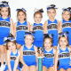 Young girls on an Xtreme Cheer team show a trophy they won at a competition last year.