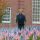 Fort Lee Public Schools' custodian Pete Sganga clears the grounds of debris and fixes the flags ahead of the Veteran's Day ceremony.