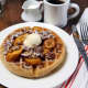 Comfort food like this plate of waffles topped with bananas and walnuts is highlighted in the menu at Judys Bar + Kitchen in Stamford.