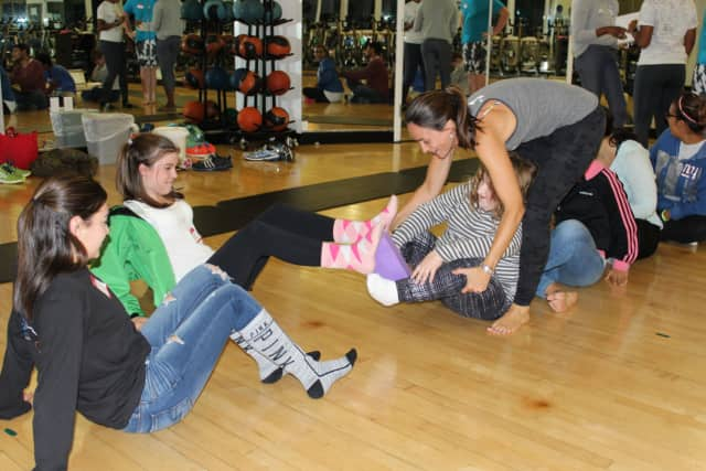 "Participants in a yoga class for children with special needs at the Darien YMCA perform a ""pass the block"" exercise. Left to right: Shea Canaday (volunteer), Melissa Hartunian (volunteer), Sarah Dorris and Talita Moss (yoga instructor)."