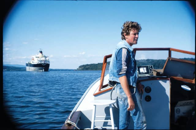 """Riverkeeper John Cronin, 1983. Photo, Don Nice. Courtesy of Riverkeeper. Beginning in 1972, the Hudson River Fishermen's Association began a """"Riverkeeper"""" program to patrol the river. Ten years later, Riverkeeper John Cronin and his boat were monitoring the river full-time. On Cronin's first day, he confronted an Exxon tanker discharging polluted ballast water into the river. In 1986, the Hudson River Fishermen's Association merged with its Riverkeeper program to form one group to protect the river. Images courtesy  New-York Historical Society Museum & Library."""