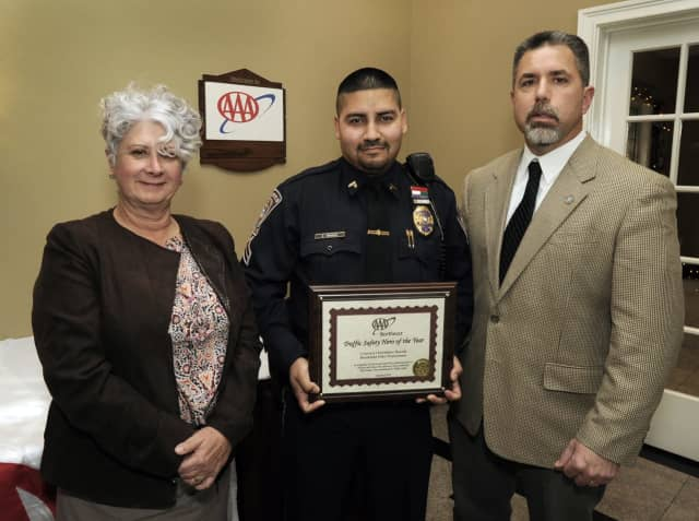 At AAA's seventh annual Community Traffic Safety Awards lunch at Testo's in Bridgeport, Public Affairs Manager Fran Mayko, left, presents Brookfield Police Cpl. Christopher Rosado with his award. At right is Brookfield Police Captain John Puglisi.