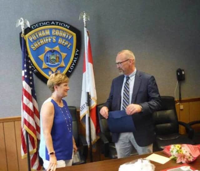 Pat Butler is congratulated by Sheriff Robert L. Langley on her retirement.