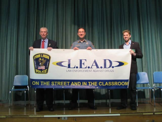 Photo: Memorial Middle School was presented with a new LEAD banner and flag during its recent graduation ceremony. From left: Mayor John Cosgrove, LEAD Officer Gerard Graziano and Councilman Kurt Peluso.