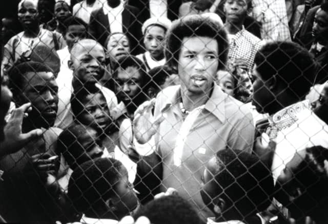 Arthur Ashe talks with young fans in Soweto, South Africa, Nov. 23, 1973. Photograph by Gerry Cranham/Getty Images.