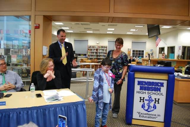 Hendrick Hudson School District Superintendent Joseph Hochreiter presents Emma Weinstein with her Student of Distinction award, as Pines Bridge teacher Carolyn Schneider looks on.