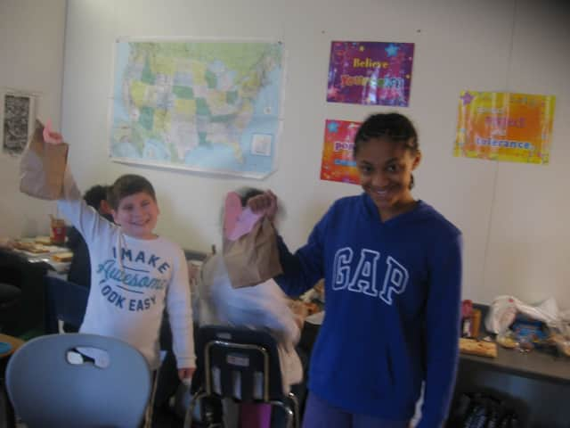 Daniel Moskowitz (left) and Amani Campbell hold up bagged lunches they prepared to be distributed to homeless people in New York City. The activity was part of a larger lesson on empathy at the Walden School in Yorktown