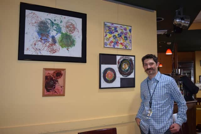 Jesse Steiner in front of artwork made by students on the autism spectrum.
