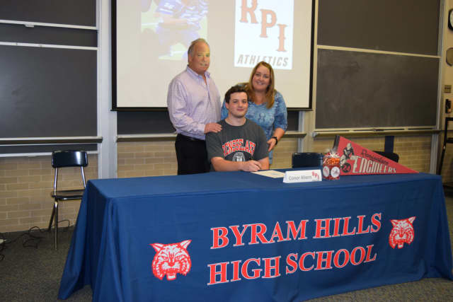 Conor Ahearn, with his parents, signed his letter of intent to play football at RPI