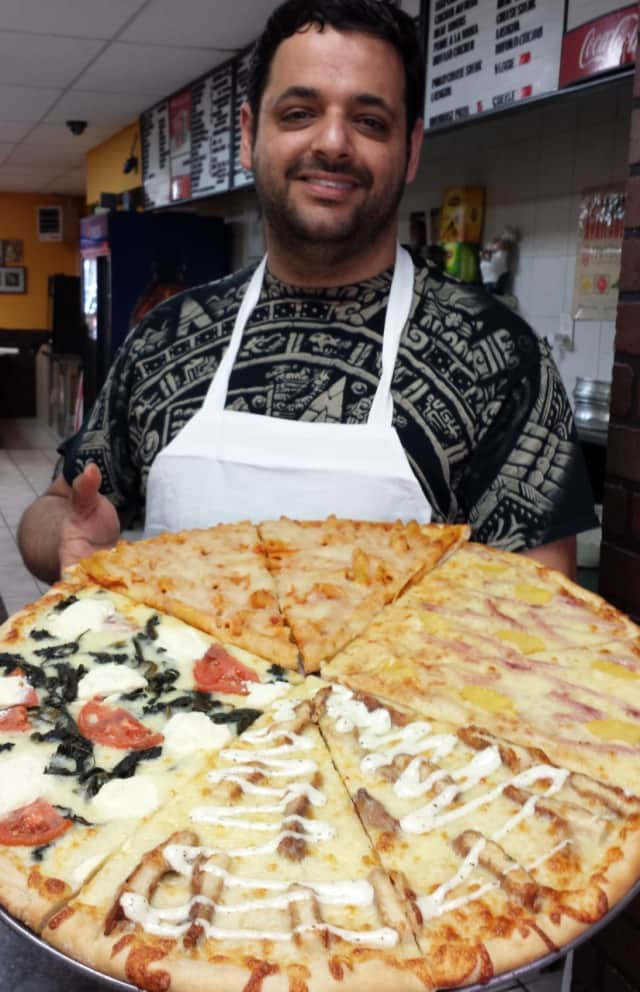 Frank Daher with a platter of many different types of pizza pies.