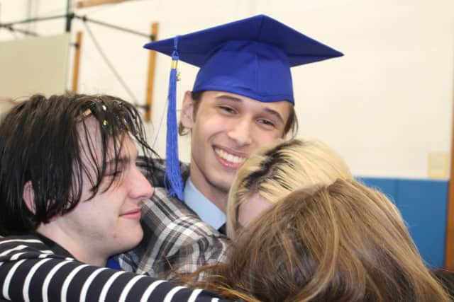 A BOCES graduate celebrates receiving his adult education diploma.