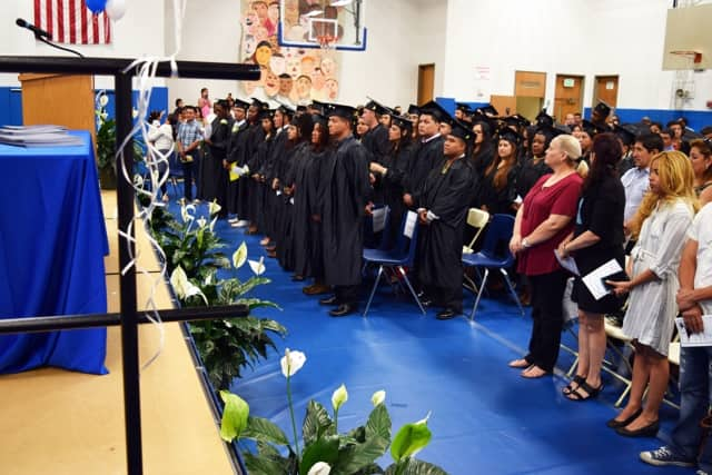 Adult Education graduates stand for the National Anthem at the Adult Education Graduation Ceremony on June 16 at Putnam/Northern Westchester BOCES.