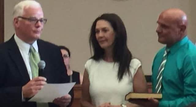 Ridgewood Attorney Matthew Rogers, left, swears in Ridgewood Mayor Susan Knudsen as her husband, John, looks on.